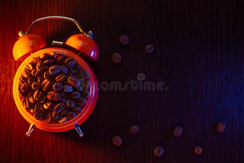 Оранжевый будильник с кофейными зернами на деревянном столе стоковые фото