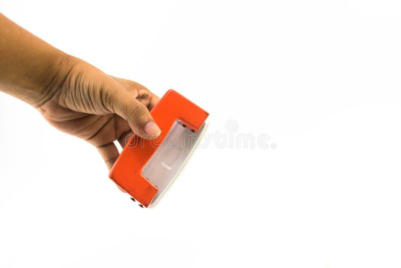 Оранжевый бумажный пунш на изолированной руке человека стоковое изображение