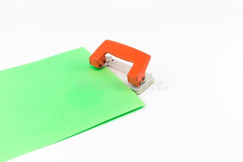 Оранжевый бумажный пунш при изолированная зеленая книга стоковые изображения rf