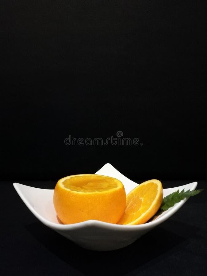Оранжевый десерт студня в выдолбленном вне апельсине и куски оранжевые на белой плите изолируют черную предпосылку, стильную еду  стоковые фотографии rf
