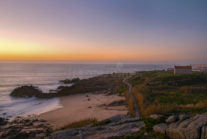 Оранжевый заход солнца на ландшафте с пляжем и церковью стоковое фото rf