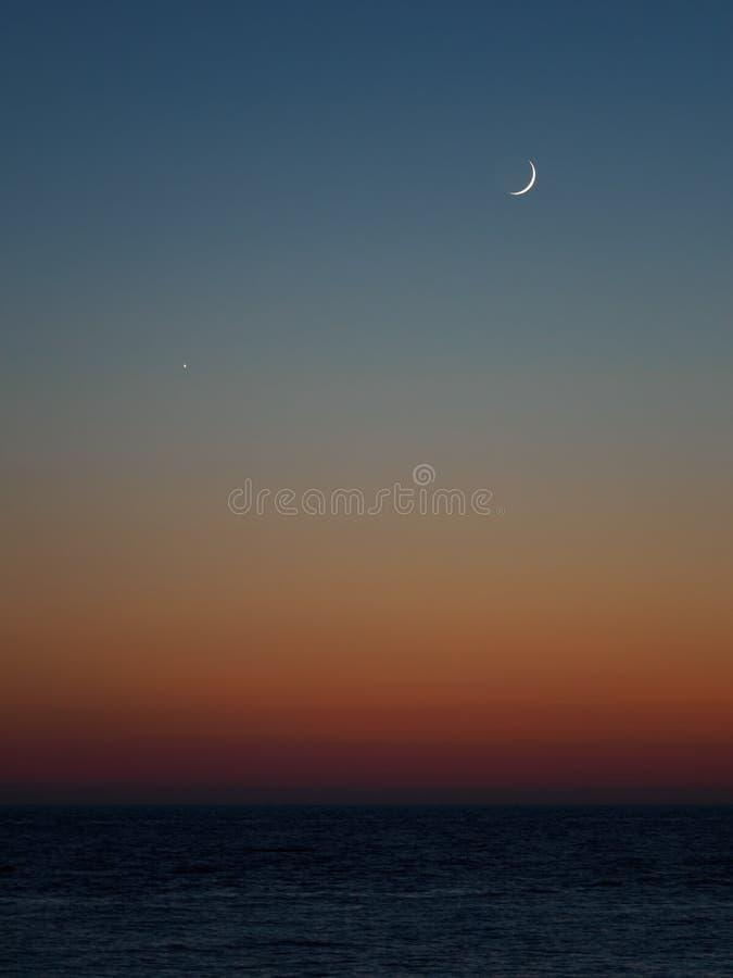 Оранжевый и голубой заход солнца в море Полумесяц над водой стоковые фотографии rf