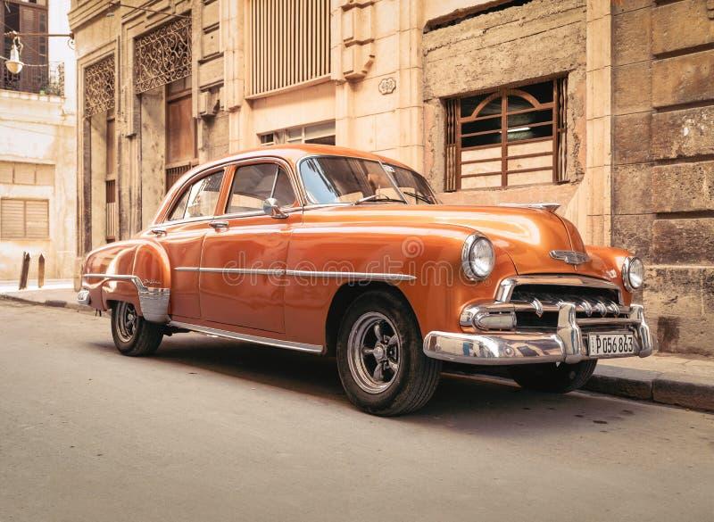 Оранжевый классический автомобиль припаркованный на улице Гаваны стоковые изображения