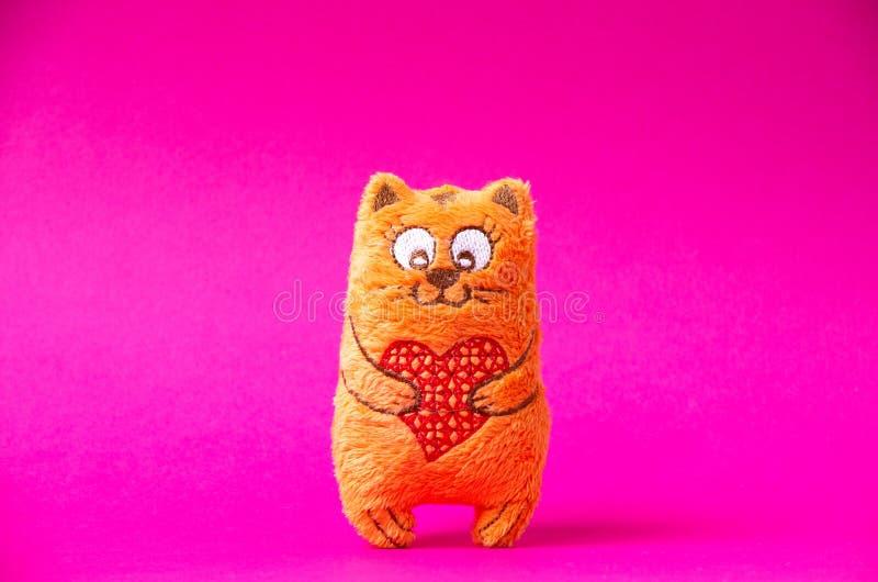 Оранжевый кот плюша с красным сердцем настолько милым на розовой предпосылке стоковые изображения rf