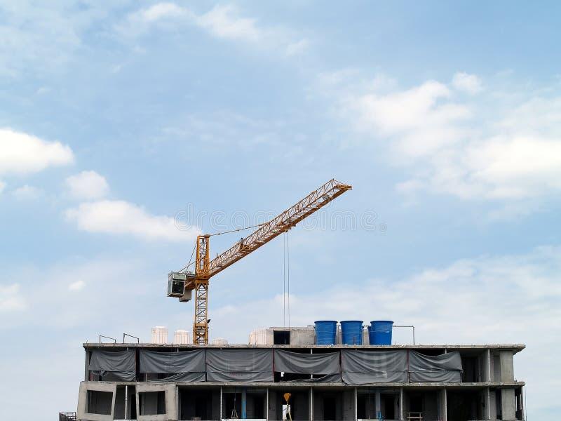Оранжевый кран башни наверху здания под конструкцией с голубым небом и облаком, многоэтажным зданием конструкции в городе стоковое фото rf