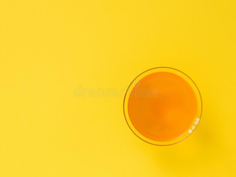 Оранжевый напиток в стекле на яркой желтой предпосылке minimalism r стоковое фото rf