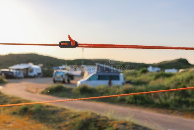 Оранжевый натяжной канат и черный регулятор держа шатер устоичивый в своем месте стоковое изображение rf