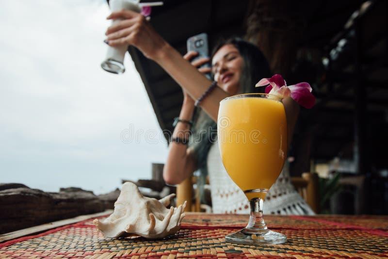 Оранжевый сок манго в стекле с цветком рядом с морем обстреливает на переднем плане стоковая фотография rf