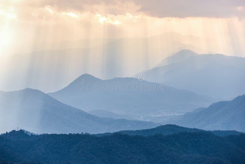 Оранжевый солнечный луч от облачного неба к голубому ряду гор стоковая фотография rf