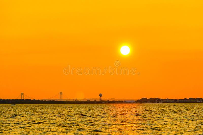Оранжевый сумрак в Нью-Йорке с взглядом моста Verrazzano-узких частей стоковое фото
