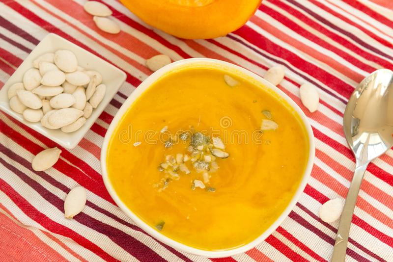 Оранжевый суп в плите, семена тыквы тыквы, красная striped скатерть, ложка стоковое изображение
