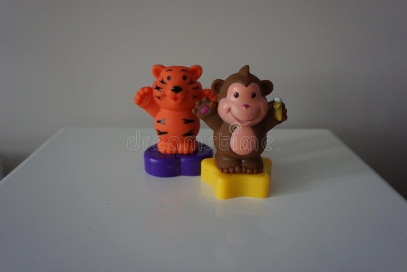 Оранжевый тигр и коричневые игрушки пластмассы обезьяны стоковое фото