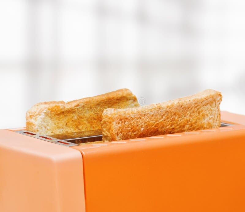 Оранжевый тостер с 2 кусками хлеба стоковая фотография rf