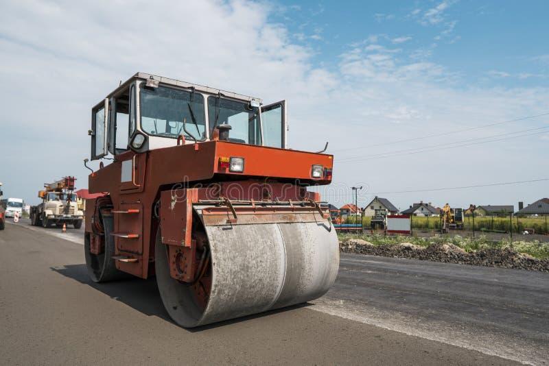 Оранжевый тяжелый compactor ролика вибрации на мостоваой асфальта работает для ремонтировать дороги Работа на новой дороге стоковые изображения