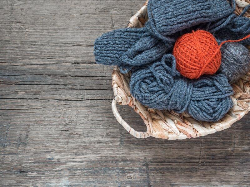 Оранжевый шарик пряжи шерстей и голубой пряжи в плетеной корзине стоковые фото