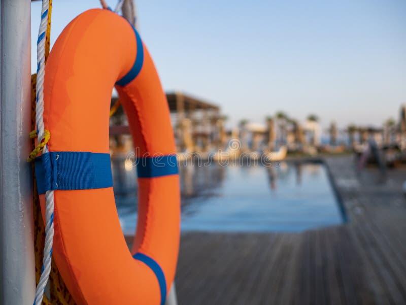 Оранжевый lifebuoy близко общественный бассейн на запачканной предпосылке, бассейн видим стоковые фото