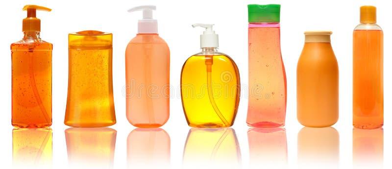 7 оранжевых пластичных бутылок с шампунем, жидкостным мылом, гелем ливня Изолировано на белой предпосылке с отражением стоковые фотографии rf