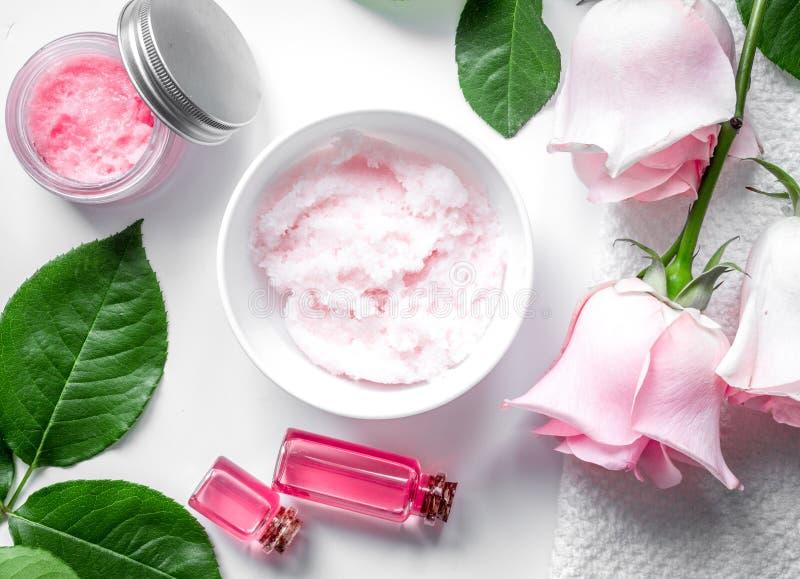 Органическая косметика с розовым маслом на белом взгляд сверху предпосылки стоковое изображение