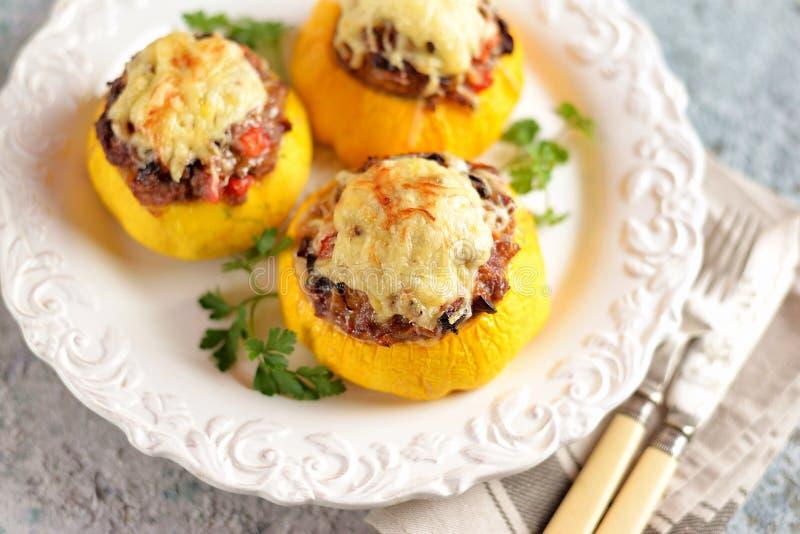 Органические желтые patissons заполненные с мясом, луками, морковами, грибами и красным перцем испекли в печи с сыром стоковые фото
