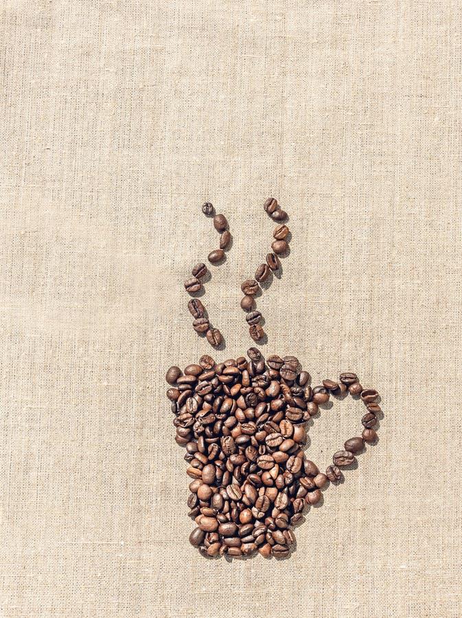 Органические зажаренные в духовке кофейные зерна и linen скатерть стоковая фотография rf