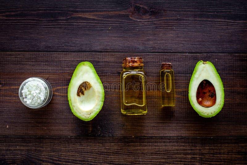 Органические косметики с естественными ингридиентами Эфирное масло авокадоа около половины авокадоа на темной деревянной верхней  стоковая фотография