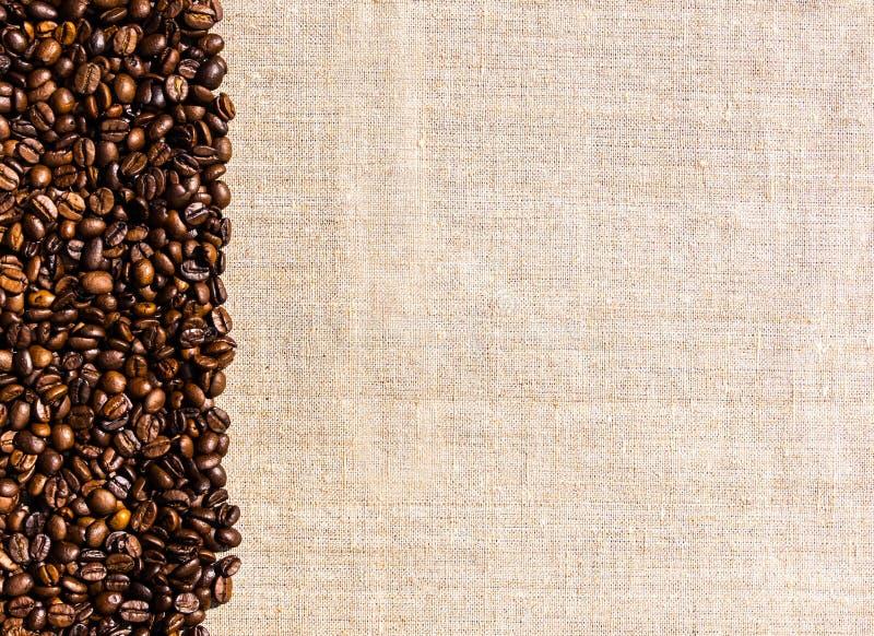 Органические кофейные зерна и linen скатерть Предпосылка и космос для текста стоковые фото