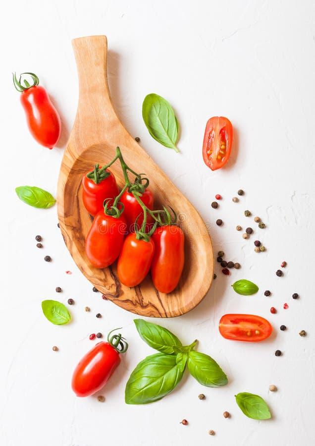Органические мини томаты Сан Marzano на лозе с базиликом и перце в плите oilve деревянной на белой предпосылке кухни стоковая фотография rf