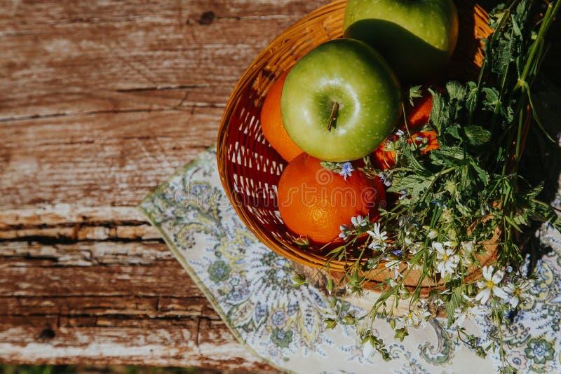 Органические яблоки в корзине в траве лета Свежие яблоки в природе стоковые изображения rf