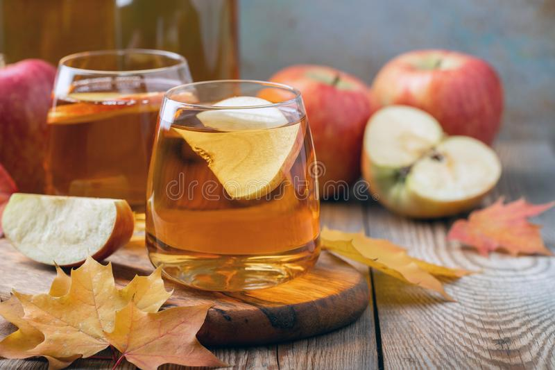 Органические яблочный сидр или сок на деревянном столе 2 стекла с листьями питья и осени на деревенской предпосылке стоковая фотография