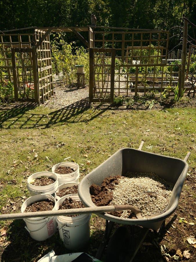 Органический огород: смешивая тачка почвы стоковое изображение