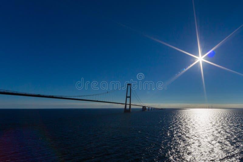Ореундский мост с голубым океаном, небом, солнцем и световыми рефлексами стоковые изображения