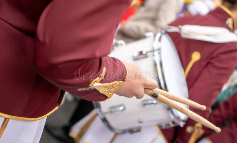 Оркестровый барабанщик в красн-белой форме с белым барабанчиком и ручками барабанчика стоковые фото