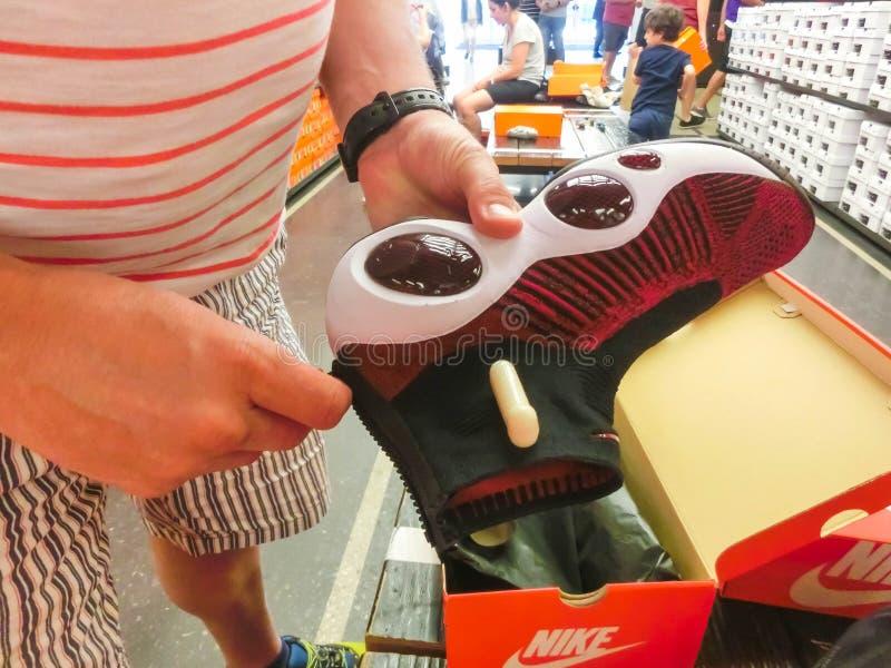 Орландо, США - 8-ое мая 2018: Человек выбирая тапки на магазине в выходе Орландо торгового центра наградном на Орландо, США стоковая фотография rf