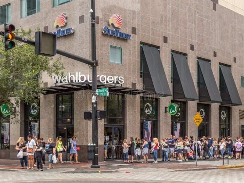 ОРЛАНДО, ФЛОРИДА - 13-ОЕ ИЮЛЯ 2019: WAHLBURGERS Длинная очередь форм людей вне нового соединения бургера в городском Орландо стоковая фотография