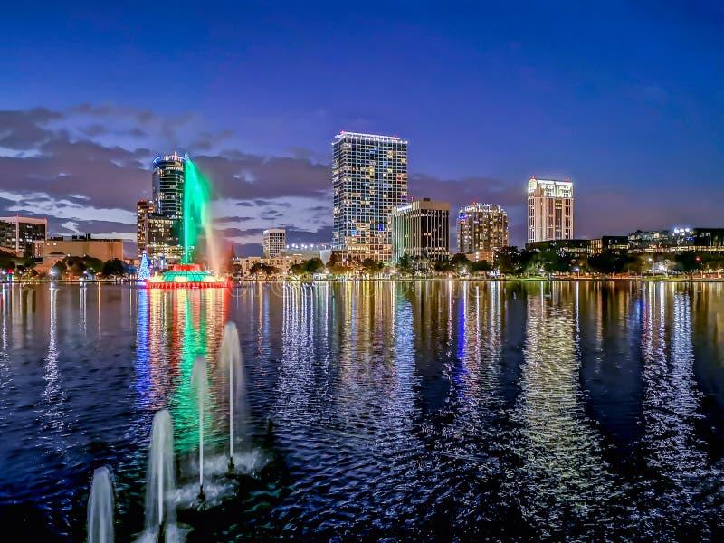 ОРЛАНДО, ФЛОРИДА, США - ДЕКАБРЬ 2018: Красочные света, после захода солнца, на парке озера Eola с фонтаном и зданиями стоковая фотография rf