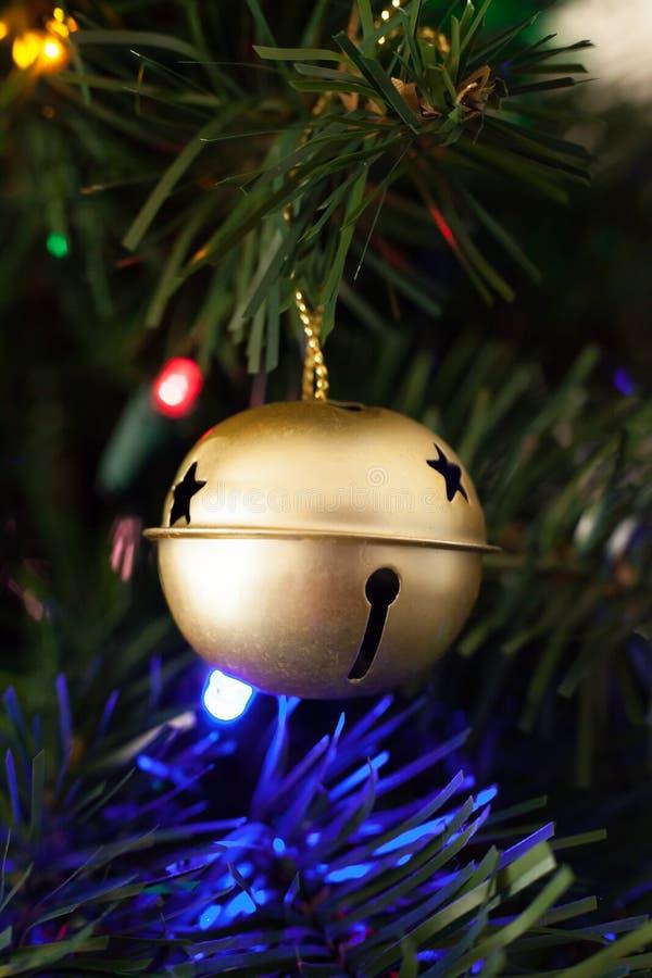 Орнамент колокола саней золота повешенный на искусственной рождественской елке стоковые фото