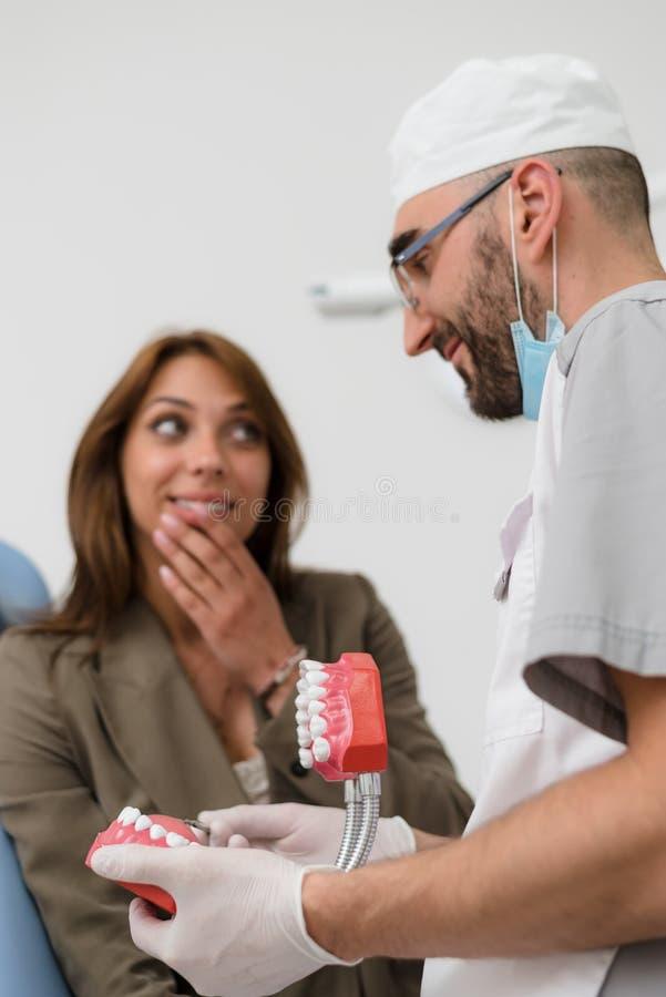 Ортодонт показывает девушку на примере человеческой челюсти, как зубы аранжированы во рте стоковые фотографии rf