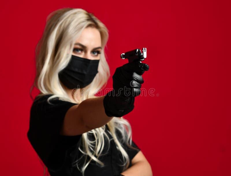 Оружие прошивкой уха владением cosmetologist beautician женщины в черных медицинских перчатках и маска на красном цвете стоковые изображения rf