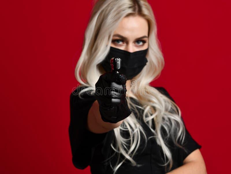 Оружие прошивкой уха владением cosmetologist beautician женщины в черных медицинских перчатках и маска на красном цвете стоковое изображение