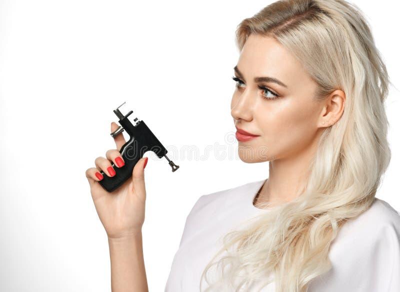 Оружие прошивкой уха владением cosmetologist beautician женщины смотря угол изолированный на белизне стоковая фотография