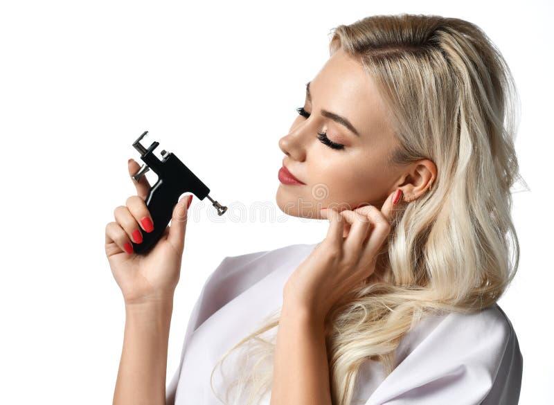 Оружие прошивкой уха владением cosmetologist beautician женщины смотря угол изолированный на белизне стоковые изображения