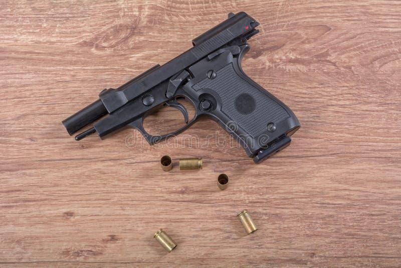 Оружие с пулями на деревянной предпосылке стоковое изображение