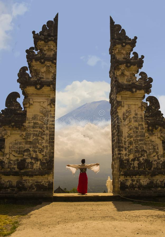 Оружия азиатской женщины распространяя перед держателем Agung вулкана Бали через красивый и величественный строб индусского Pura  стоковое фото