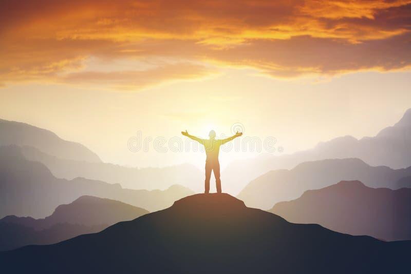 Оружия альпиниста вверх протягиванные на верхней части горы смотря вдохновляющий ландшафт стоковое фото
