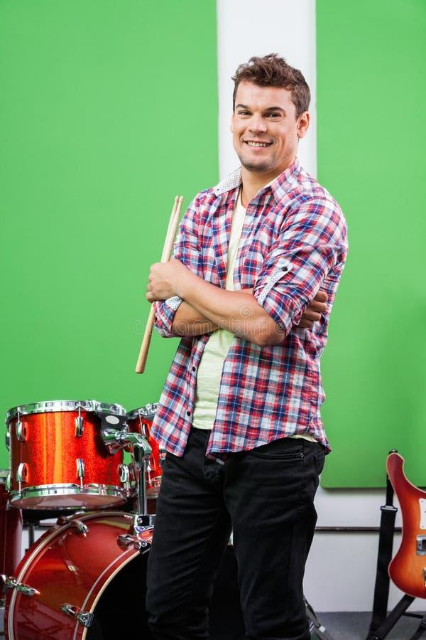 Оружия барабанщика стоящие пересеченные в студию звукозаписи стоковая фотография
