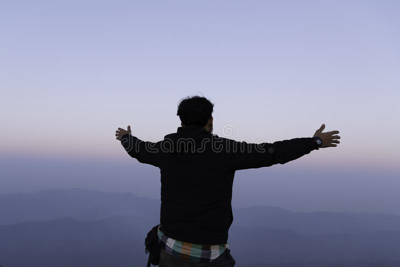 Оружия благодарного человека открытые к стойке восхода солнца стоковое фото