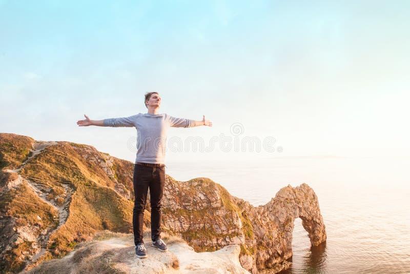 Оружия молодого человека подняли до неба, празднуя свободу стоя на утесе с взглядом двери Durdle на заходе солнца Положительное f стоковая фотография rf