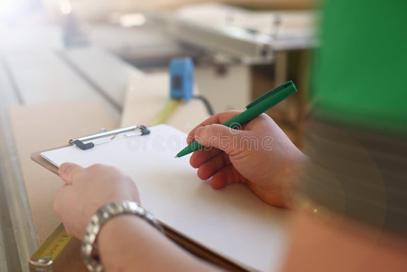 Оружия работника делая примечания на доске сзажимом для бумаги с зеленой ручкой стоковая фотография rf