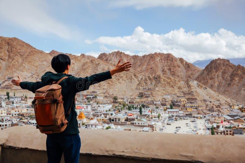 Оружия счастливого молодого путешественника распространяя в предпосылке города в Leh, Ladakh, Индии стоковое изображение rf