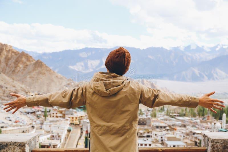 Оружия счастливого молодого путешественника распространяя в предпосылке города в Leh, Ladakh, Индии стоковая фотография